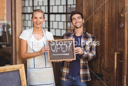 Smiling waitress and man holding chalkboard with open sign