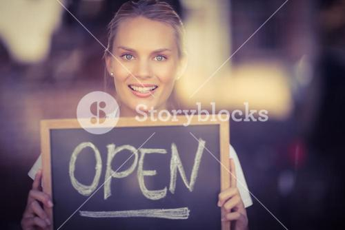 Smiling blonde waitress showing chalkboard with open sign