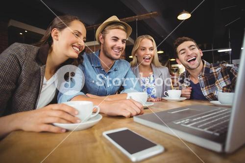 Laughing friends looking at laptop screen