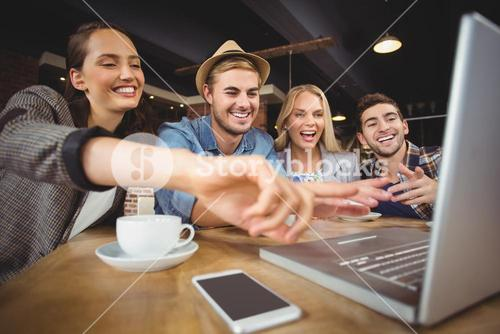 Laughing friends looking at laptop and pointing at screen