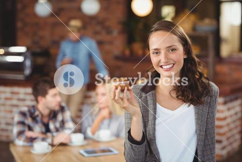 Smiling young woman holding muffin