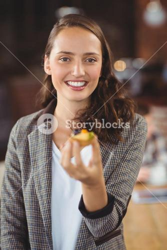 Smiling young woman showing muffin