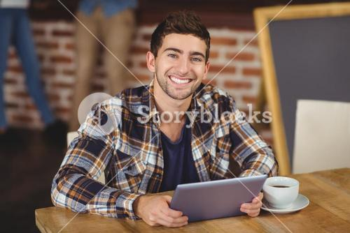 Smiling hipster using tablet computer