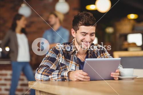 Smiling hipster sitting and using tablet computer