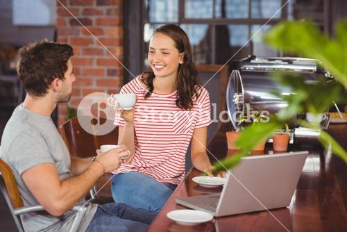 Smiling friends drinking coffee and chatting