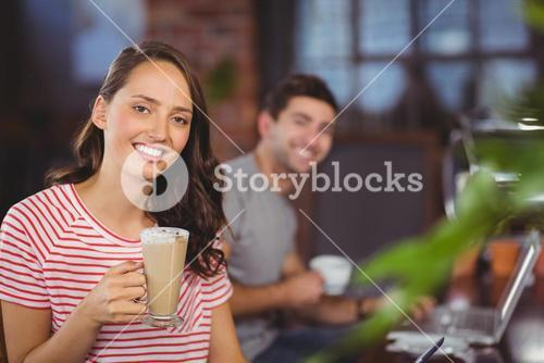 Smiling young woman with latte