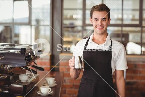 Smiling barista holding jug with milk