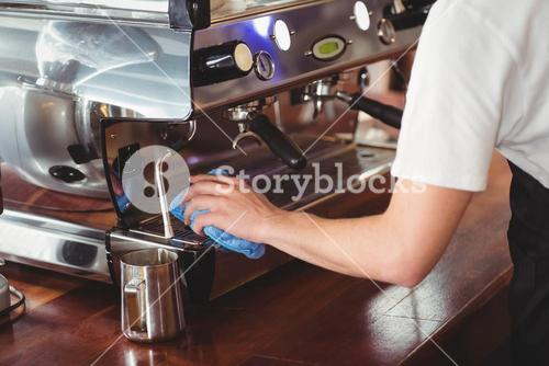 Barista cleaning coffee machine