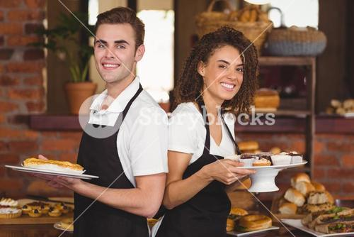 Smiling waiter and waitress holding plates with treat