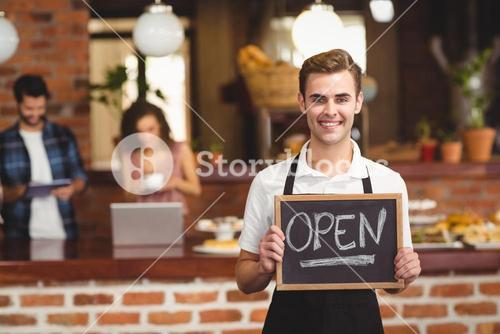 Smiling barista holding chalkboard with open sign