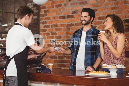 Smiling hipster giving credit card to barista