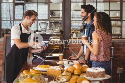 Smiling barista taking credit card from hipsters