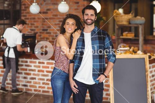 Smiling hipster couple in front of barista