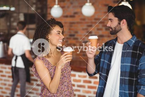 Smiling hipster couple with take-away cups