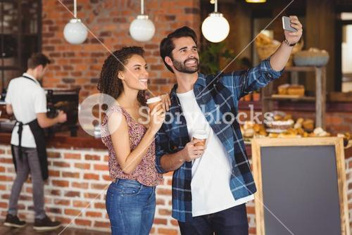 Smiling hipster couple taking selfies