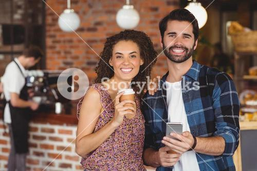 Smiling hipster couple holding smartphone