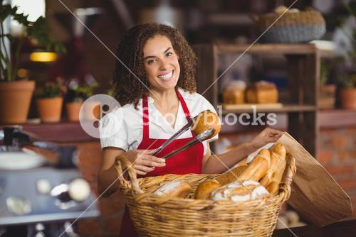 Smiling waitress picking up bread from a basket