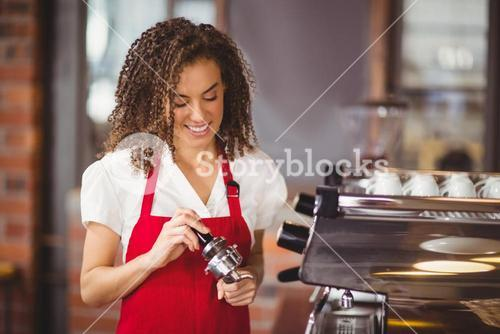 A smiling barista pressing coffee