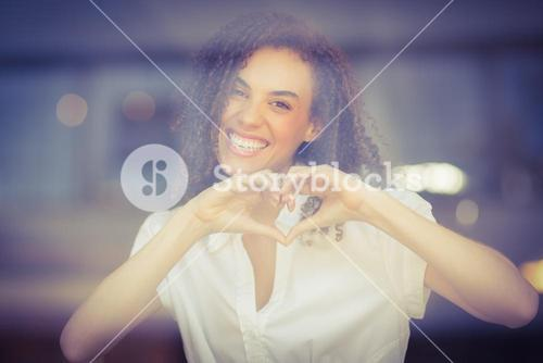Smiling woman making heart shape