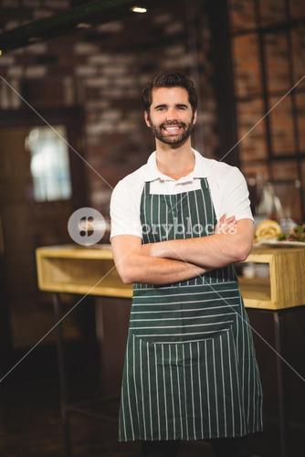 Smiling barista with arms crossed