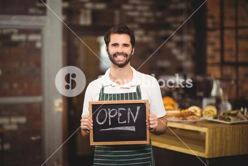 Smiling waiter showing chalkboard with open sign