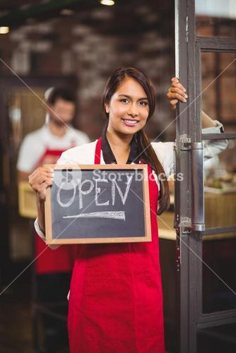 Smiling waitress showing chalkboard with open sign
