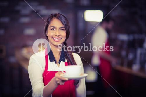 Smiling waitress handing a cup of coffee