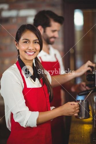 Smiling waitress steaming milk at the coffee machine