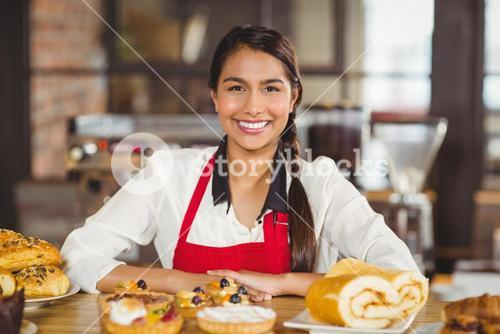 Smiling waitress standing over pastries