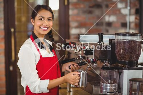 Smiling barista steaming milk at the coffee machine