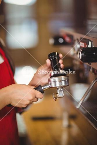 Close up of a barista pressing coffee