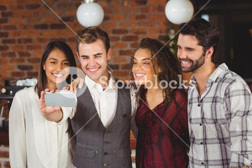 Smiling friends taking a selfie together