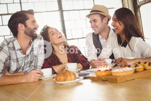 Laughing friends enjoying coffee and treats