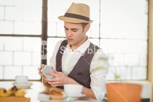 Concentrated hipster using smartphone