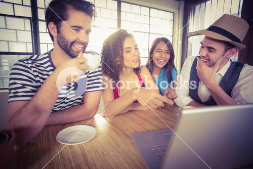 Laughing friends drinking coffee and looking at laptop