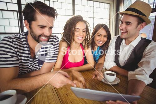 Laughing friends pointing and looking at tablet computer