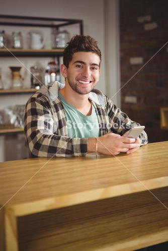 Smiling hipster using smartphone