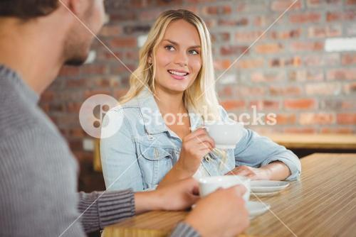 Smiling blonde having coffee with friend