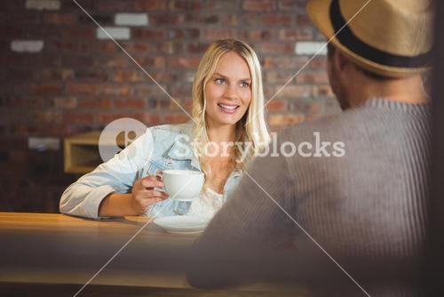 Smiling blonde drinking coffee with friend