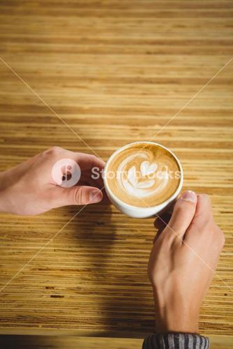 Hands holding cappuccino with coffee art