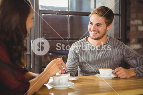 Handsome man enjoying cake and coffee with friend