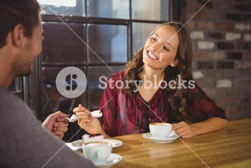 Pretty brunette enjoying cake and coffee with friend