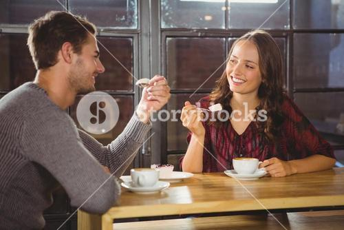 Smiling friends enjoying coffee and cake together