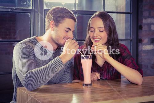 Smiling friends sharing smoothie