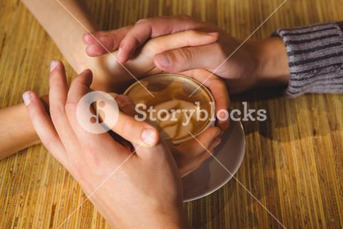 Couple holding hands around cappuccino with coffee art