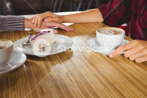 Couple holding hands and having coffee and cake together