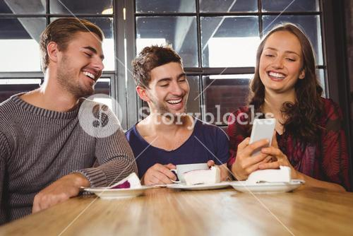 Laughing friends looking at smartphone