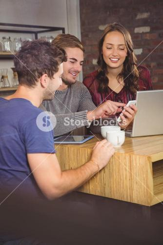 Smiling friends looking at smartphone