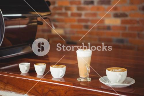 Several hot beverages in a row on the counter