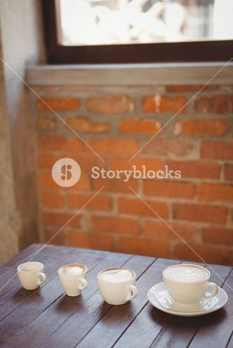 Several hot beverages in a row on wooden table